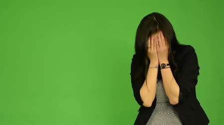 kötü : young attractive asian woman cries - green screen studio