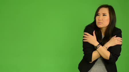 üzleti öltöny : young attractive asian woman shivers - cold - green screen studio