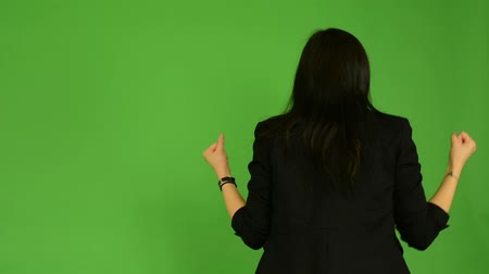 regozijo : young attractive asian woman rejoices (back) - green screen studio