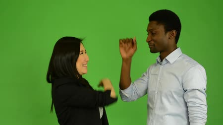 пять : Happy couple high five and smile to camera - black man and asian woman - green screen studio