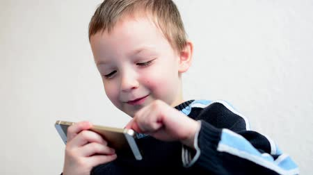 gry komputerowe : little boy plays games on the smartphone - closeup