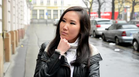 szándékozik : young attractive asian woman thinks - urban street with cars - city