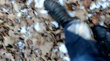 walking man : fallen leaves on the ground with snow - man walking - shot on foot Stock Footage