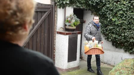 przesyłka : Seller carries product of pasta (in basket) to customer in home