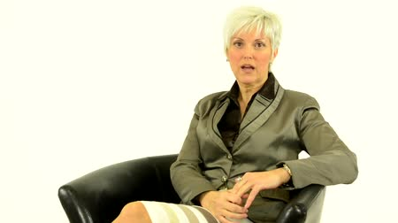 deneyim : business middle aged woman sits and talks to camera (interview) - white background - studio