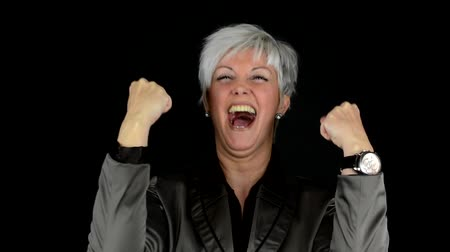 kutluyor : business middle aged woman rejoices (joy) - black background - studio Stok Video
