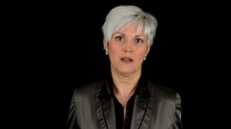 rozhovor : business middle aged woman talks to camera (interview) - black background - closeup - studio Dostupné videozáznamy