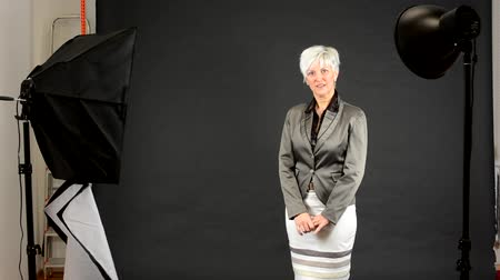 lighting up : studio - photographic equipment (light and reflecting plate) - business woman - black background