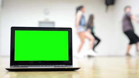 экран : notebook - green screen -  three dancers - group of three friends dance in background - two women and one man - hall Стоковые видеозаписи
