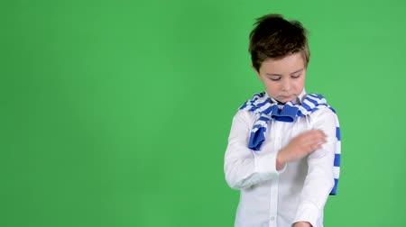 ubrania : young handsome child boy adjusts his clothes and smiles to camera - green screen - studio