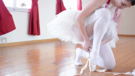 положить : young ballerina puts on ballet shoes and ballerina ties shoes