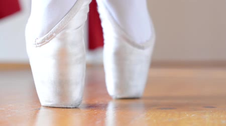 balerína : ballerina dancing in the hall - closeup - detail of foot (shoes) - parquet block