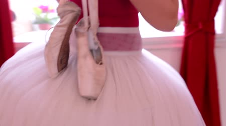 определенный : ballerina carries ballet shoes over shoulder - interior - red curtain