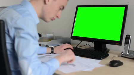 masaüstü : man works on desktop computer in the office - typing on keyboard - green screen