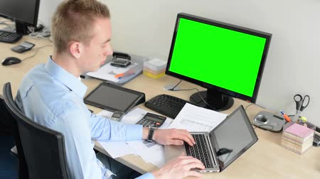 masaüstü : young handsome man works on laptop computer in the office - green screen - desktop computer and tablet