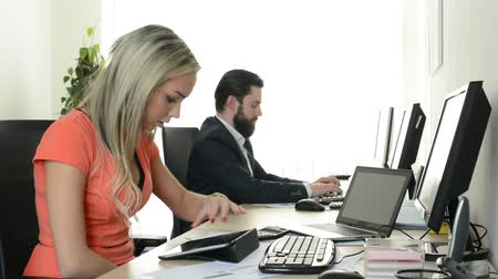 применения : woman works on tablet and man works on desktop computer in the office (workers) Стоковые видеозаписи
