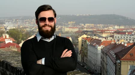 okulary przeciwsłoneczne : young handsome man with full-beard (hipster) puts on his sunglasses and smiles - city in background