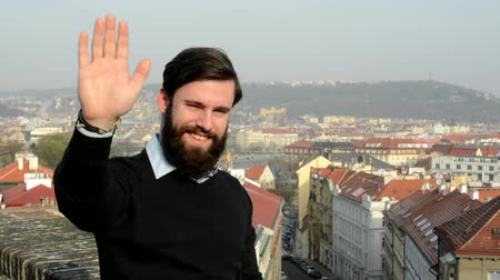Прага : young handsome man with full-beard (hipster) waves with hand for greeting - city in background