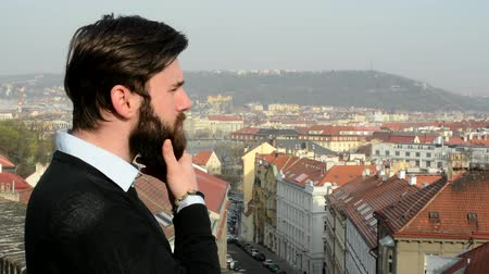 борода : young handsome man with full-beard (hipster) look at the city and meditates - city in background