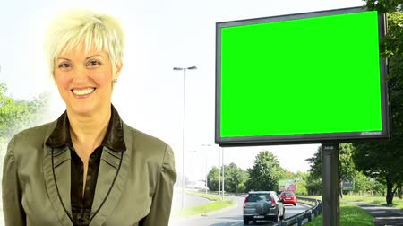 гласность : business middle aged woman smiles  billboard  green screen  urban street with passing cars and buildings