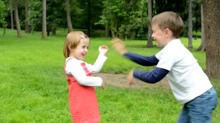 родной брат : children siblings - little boy and cute girl playing in the park siblings tickle