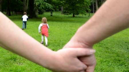 small park : family - man and woman holding hands - detail - children siblings - little boy and cute girl playing in the park in the background Stock Footage