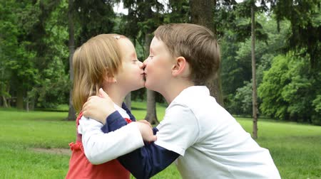 o : children siblings - boy and girl give a kiss in park