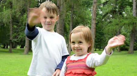 good : childrens young boy and little girl siblings wave with hands and smile to camera - park Stock Footage