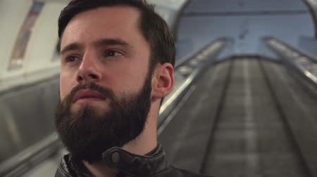 broda : Young handsome hipster man travels on the escalator in the subway