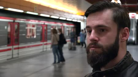 approaching subway : Young handsome hipster man waits for subway and looks around - arriving subway - people enter and leave the subway Stock Footage