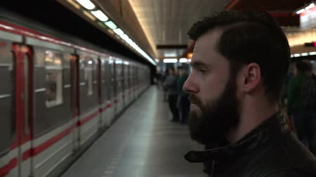 approaching subway : Young handsome hipster man waits for subway and looks around - arriving metro