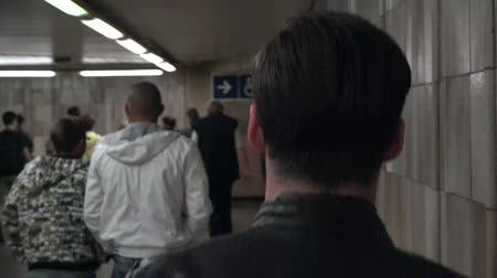bas : Young handsome hipster man walking in subway station corridor - other people in background - shot from the back - shakes shot