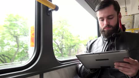 viagens de negócios : Young handsome hipster man travel by tram and works on tablet