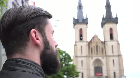 středověký : Young handsome hipster man looks at the church - city - shot from back