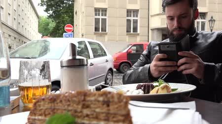 fotografando : Young handsome hipster man photographs food cake with smartphone - outdoor seating restaurant