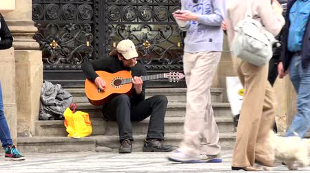 yoksulluk : PRAGUE, CZECH REPUBLIC - MAY 30, 2015: homeless street artist playing guitar - city - urban street: people walking