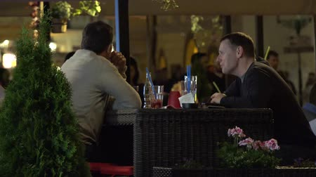 two people talking : PRAGUE, CZECH REPUBLIC - MAY 30, 2015: two men sitting in a restaurant and talking - urban street with people walking