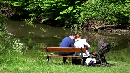 sáně : PRAGUE, CZECH REPUBLIC - MAY 31, 2015: The family relaxing near pond - Mather and father with baby sit on bench - baby carriage Dostupné videozáznamy