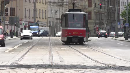 parke taşı : PRAGUE, CZECH REPUBLIC - MAY 31, 2015: urban street with passing cars and trams in the city - building in the background