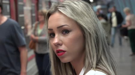 получать : young attractive blonde woman waits for subway and looks around - arriving subway - people enter and leave the subway - woman gets on a subway train unit