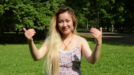 приехать : Happy attractive young asian woman in the park shows: come here Стоковые видеозаписи