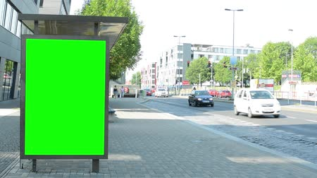 billboards : bus stop billboard with green screen in the tranquil part of the city - Slowly cars pass around Stock Footage