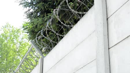 zeď : view of the solid wall with barbed wire in the countryside