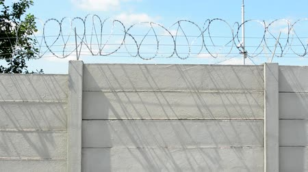 farpado : tall concrete block wall with barbed wire in the countryside Stock Footage