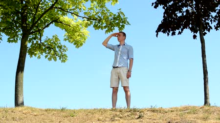 inclinado : young handsome man comes to hillock stands between trees and observes surroundings