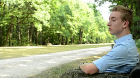 Handsome man sits in the park and looks around Stock Footage