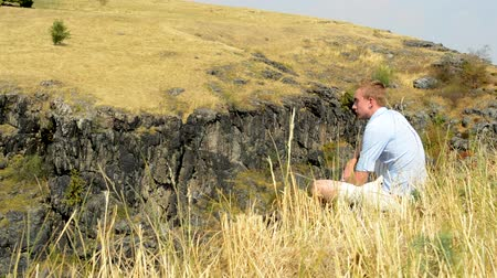 young man sits in the golden grassland on the top of the mountain - breeze shakes with grass