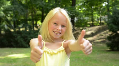 polegar : little happy girl shows thumbs up in the park near by the city - support - close up