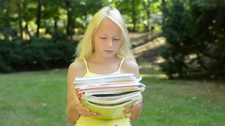 parque : little girl holds many books in the park - she is tired because she has to much school duties -  eye contact