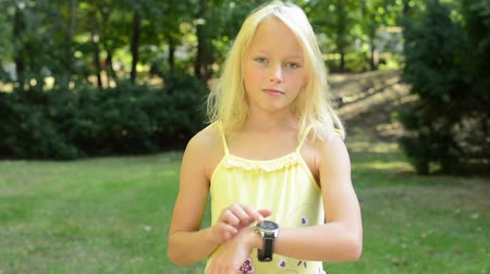 ideges : little cute girl points the watches on her hand - she points out the time - delay - eye contact Stock mozgókép